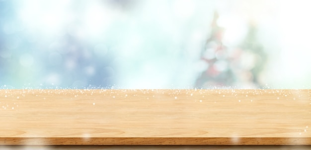 Leere hölzerne bretttischplatte mit abstraktem bokeh unschärfeweihnachtsbaum- und schneefall