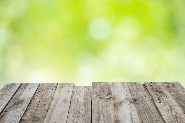 Leere hölzerne decktabelle mit laub bokeh hintergrund