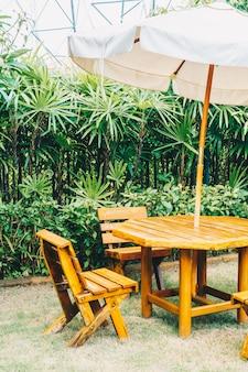 Leere hölzerne patiotabelle im freien und stuhl im hausgarten