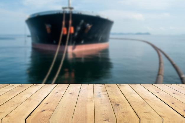 Leere hölzerne plankentabelle mit öltanker-schiffsunschärfehintergrund