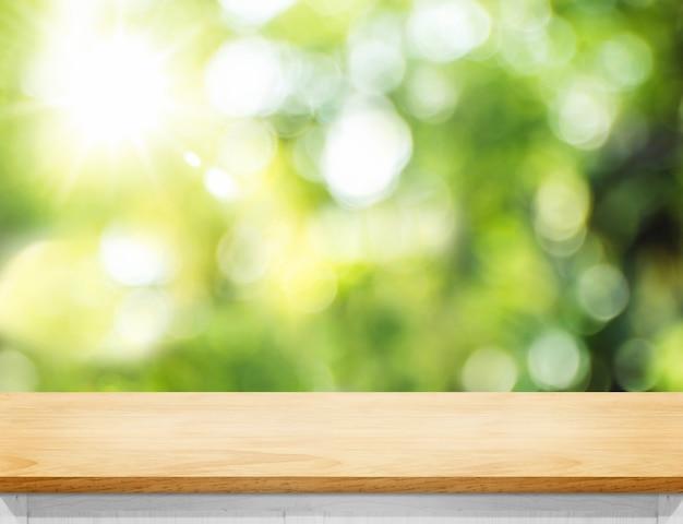 Leere hölzerne plankentischplatte mit unschärfebaum im park