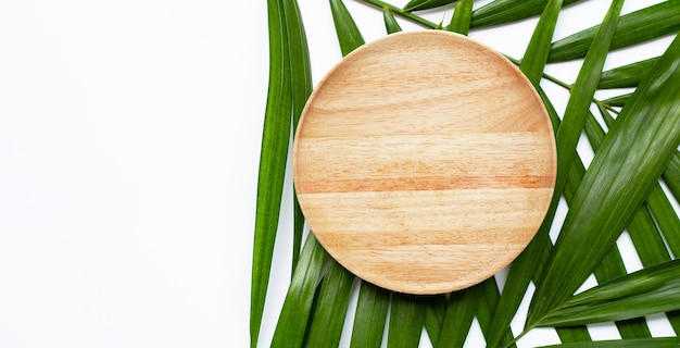 Leere hölzerne platte auf tropischen palmblättern auf weißem hintergrund. draufsicht