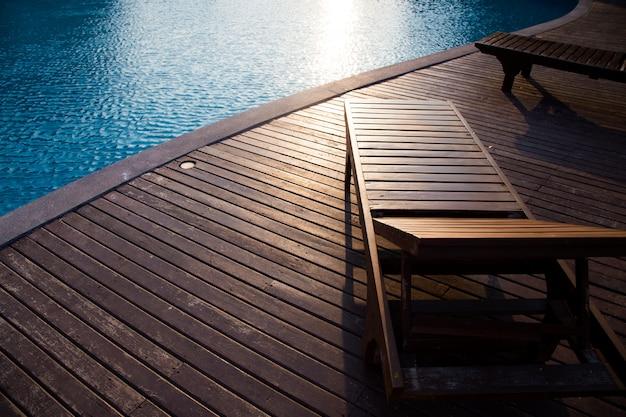 Leere hölzerne plattform und stuhl mit swimmingpool