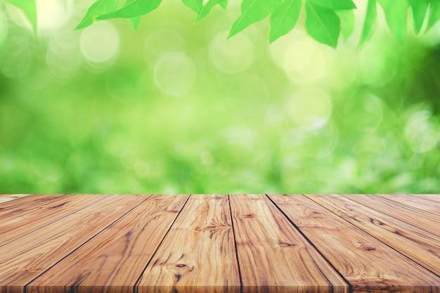 Leere hölzerne plattformtischplatte auf grün unscharfem abstraktem hintergrund vom laubhintergrund