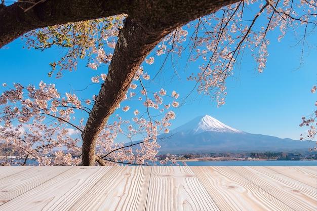 Leere hölzerne tabelle mit fuji-berg und schöner rosa jahreszeit des kirschblüten-blumenhintergrundes im frühjahr