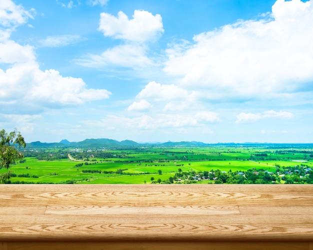Leere hölzerne tabelle mit grünem feld und blauer himmel am hintergrund