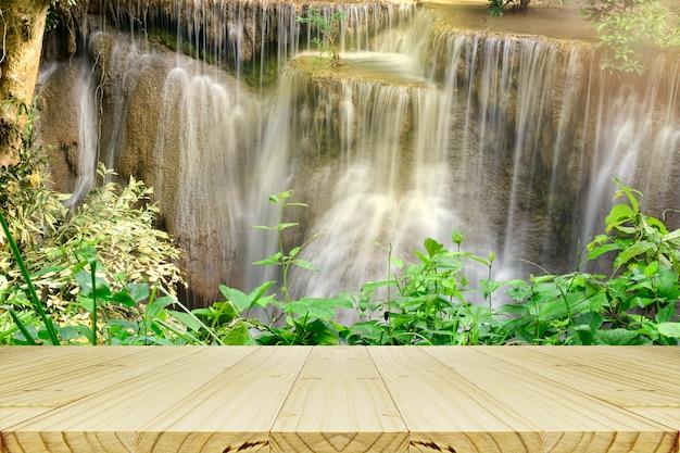 Leere hölzerne tabelle mit schönem szenischem der wasserfall- und grünblätter.