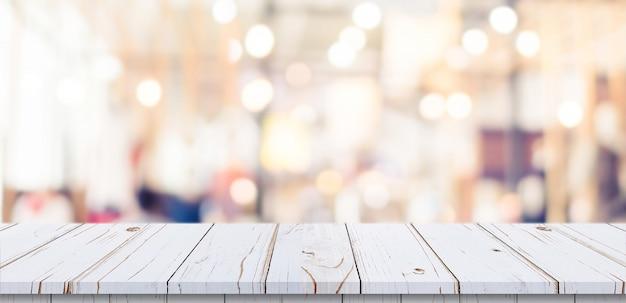 Leere hölzerne tabelle und unscharfer leuchtpult im einkaufszentrum mit bokeh hintergrund