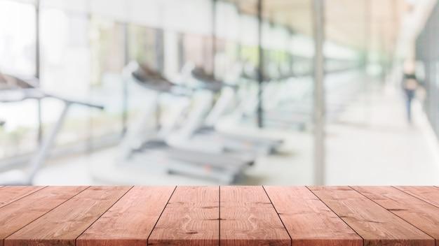 Leere hölzerne tischplatte an verwischt mit bokeh übungsraum, fitnees und turnhalleninnenfahnenhintergrund - kann für anzeige oder montage ihre produkte verwendet werden