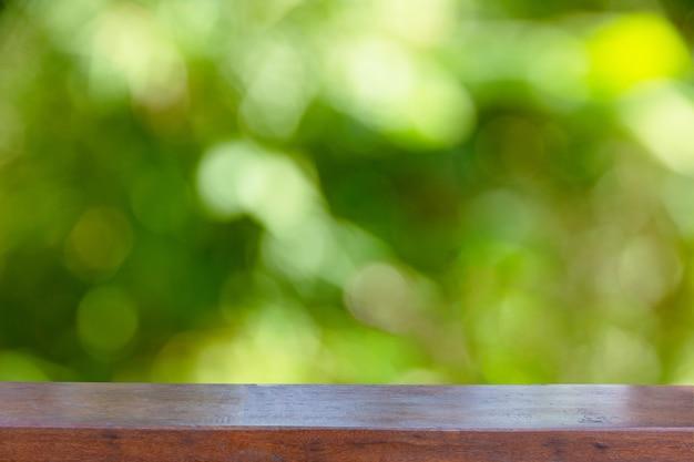 Leere hölzerne tischplatte auf abstraktem unscharfem grün vom baum
