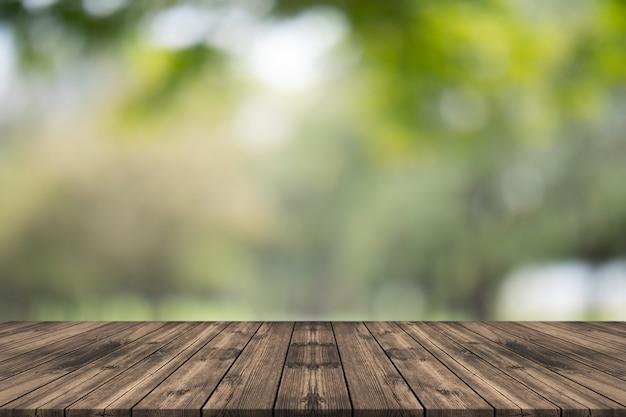 Leere hölzerne tischplatte auf dem naturgrün verwischt