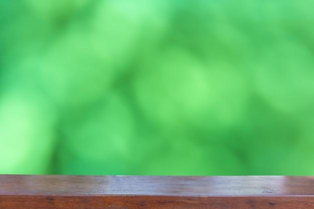Leere hölzerne tischplatte auf zusammenfassung unscharfem grünem bokeh hintergrund
