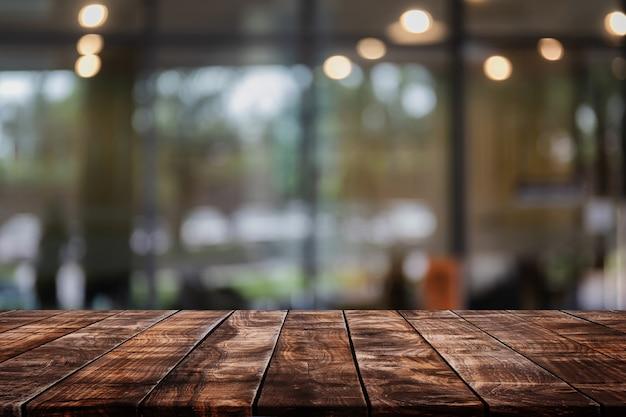 Leere hölzerne tischplatte auf zusammenfassung unscharfem restaurant- und caféhintergrund - kann für anzeige verwendet werden oder ihre produkte montieren