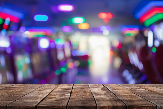 Leere hölzerne tischplatte auf zusammenfassung verwischte spielmitte shop und nachtklub beleuchtet hintergrund.