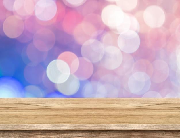 Leere hölzerne tischplatte mit abstraktem rosa, purpurrotem pastell-bokeh lichthintergrund