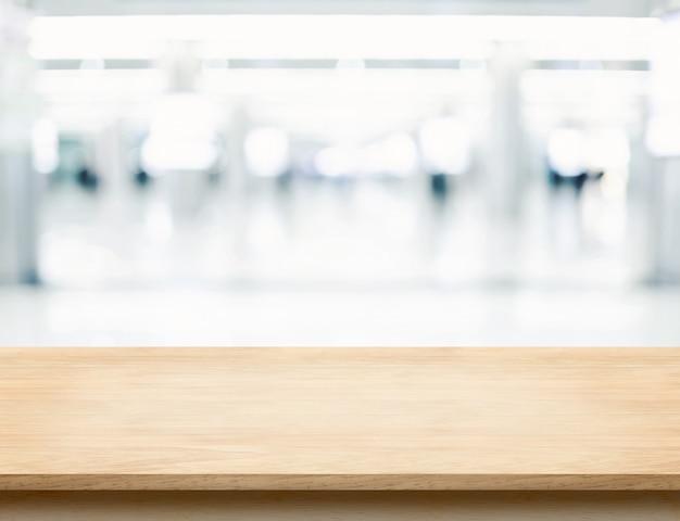 Leere hölzerne tischplatte mit bürohaushallen-weisenunschärfehintergrund