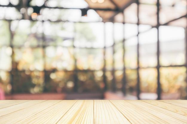 Leere hölzerne tischplatte mit der abstrakten unschärfe des café-restaurantcafés, die mit hellem hintergrund des bokehs für montageproduktanzeige defokussiert wird