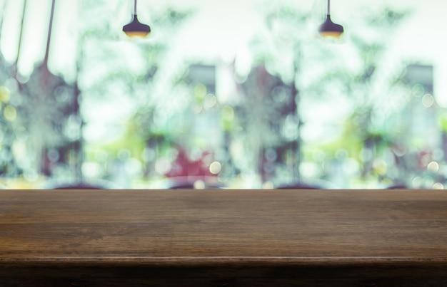 Leere hölzerne tischplatte mit unscharfem caférestauranthintergrund