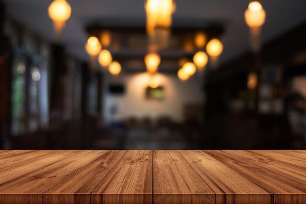 Leere hölzerne tischplatte mit unscharfem kaffeehaus- oder restaurantinnenhintergrund. kann produktanzeige verwendet werden.