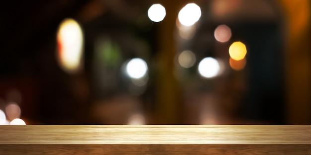 Leere hölzerne tischplatte mit unscharfem kaffeehaus oder restaurantinnenhintergrund, panoramafahne. der abstrakte hintergrund kann zur anzeige oder montage ihrer produkte verwendet werden.