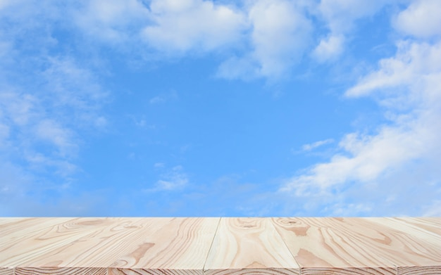 Leere hölzerne tischplatte und hintergrund des blauen himmels mit copyspace für anzeige oder montieren ihre produkte