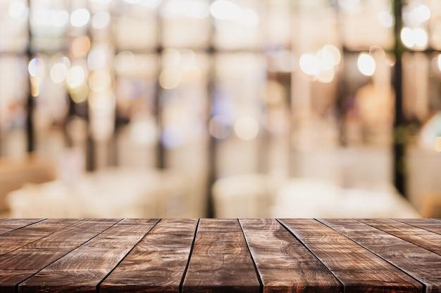 Leere hölzerne tischplatte und unscharfer bokeh café- und restaurierungsinnenhintergrund mit weinlesefilter