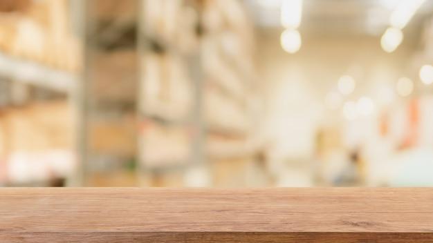 Leere hölzerne tischplatte und unscharfer innenraum des bokeh lagers