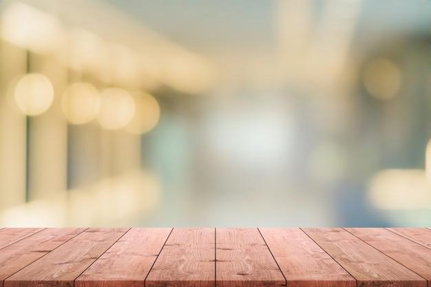 Leere hölzerne tischplatte und unscharfer kaffeestube- und restaurantinnenhintergrund - können sie für die anzeige oder montage ihrer produkte verwenden.