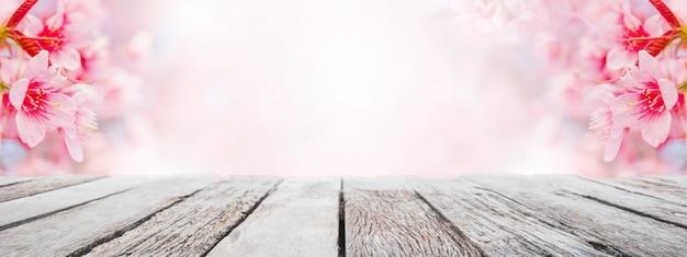 Leere hölzerne tischplatte und unscharfer kirschblüte-blumenbaum im gartenfahnenhintergrund
