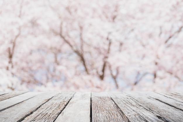 Leere hölzerne tischplatte und unscharfer kirschblüte-blumenbaum im gartenhintergrund mit weinlesefilter - können sie verwendet für anzeige oder montieren sie ihre produkte.