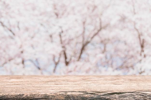 Leere hölzerne tischplatte und unscharfer kirschblüte-blumenbaum