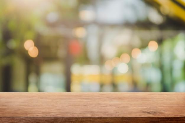 Leere hölzerne tischplatte und unscharfer restaurantinnenhintergrund