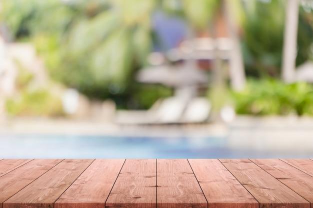 Leere hölzerne tischplatte und unscharfer swimmingpool im tropischen erholungsorthintergrund.