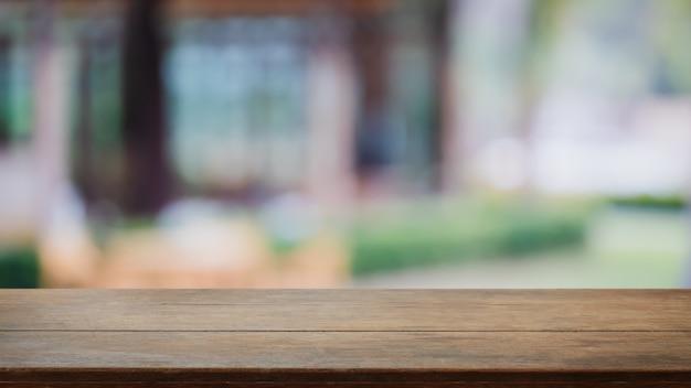 Leere hölzerne tischplatte und verwischen sie glasfenster außen im freien restaurant banner verspotten abstrakten hintergrund
