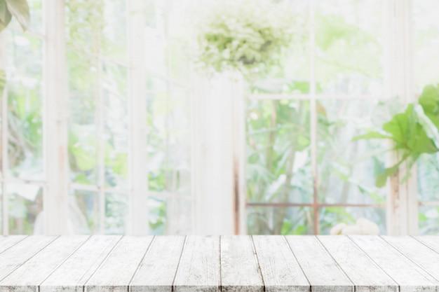 Leere hölzerne tischplatte und verwischt vom innenraum mit fensteransichtgrün vom baumgarten-hintergrundhintergrund
