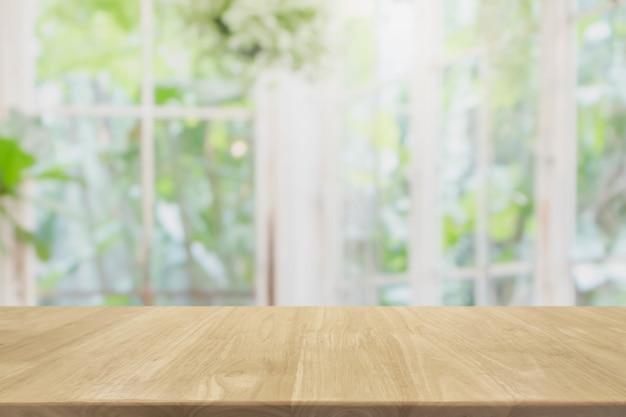 Leere hölzerne tischplatte und vom innenraum mit fensteransicht verwischt