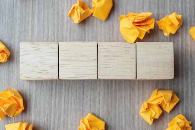 Leere hölzerne würfel mit zerfallenem papier auf holztisch