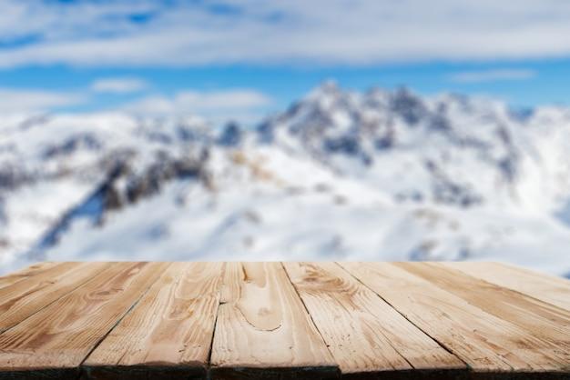 Leere holzoberfläche auf dem hintergrund des schneebedeckten bergigen geländes