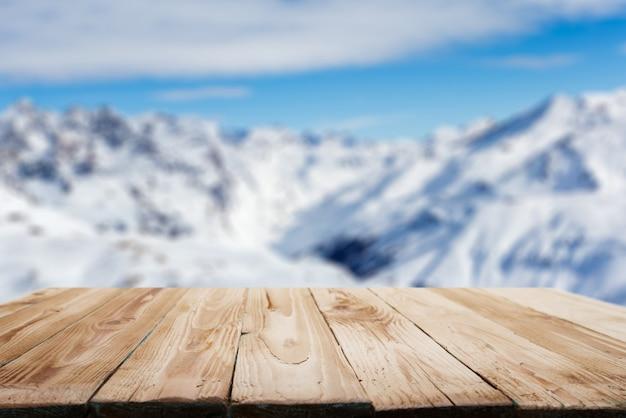 Leere holzoberfläche auf dem hintergrund des schneebedeckten hochlandes am nachmittag