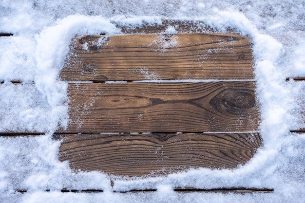 Leere holzplanke mit schneebedecktem rand, kopierraum für text