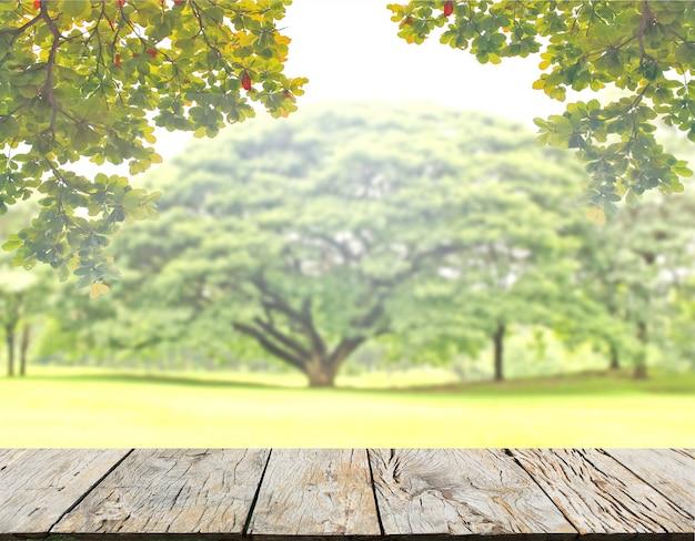 Leere holzplankentischplatte mit grüner natur hinterlässt hintergrund und unscharfen baum