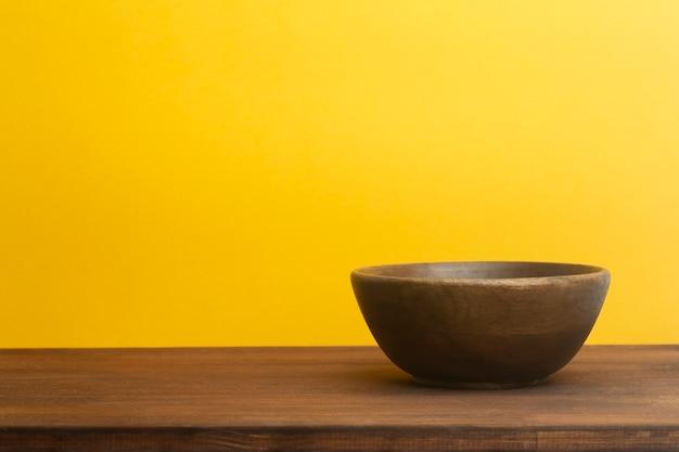 Leere holzschale auf gelbem hintergrund. holzteller auf dem tisch