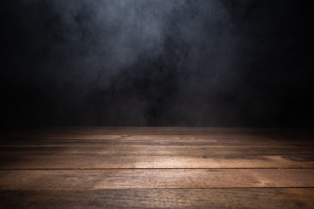 Leere holztabelle mit rauch, der auf dunklem hintergrund schwebt