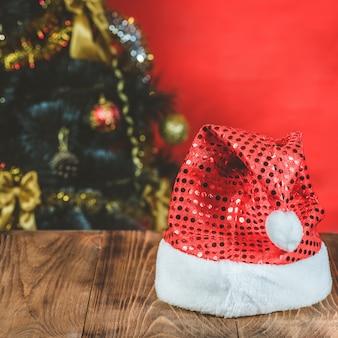 Leere holztabelle mit weihnachtsfeiertagsbaum auf rotem hintergrund. platz für produktmontage.