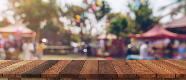 Leere holztabelle und defokussiertes bokeh und unscharfer hintergrund von gartenbäumen im sonnenlicht, montage für produkt anzeigen.