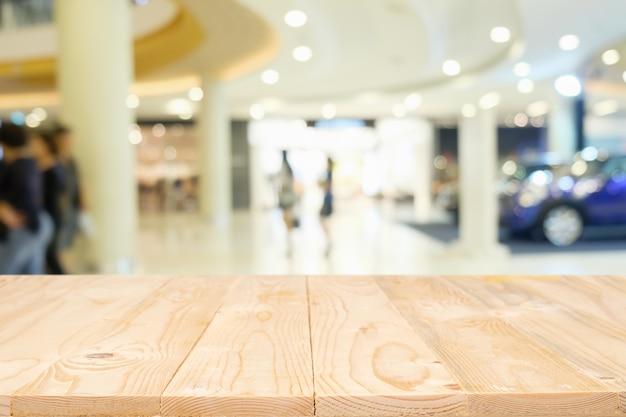 Leere holztisch platz plattform mit verschwommenes einkaufszentrum oder einkaufszentrum hintergrund für produkt-display montage. hölzerner schreibtisch mit kopie raum.