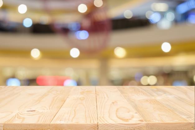 Leere holztisch platz plattform und verschwommenes einkaufszentrum oder einkaufszentrum hintergrund für produkt-display montage. hölzerner schreibtisch mit kopie raum.