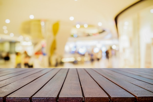Leere holztisch platzplattform und verschwommenes einkaufszentrum oder einkaufszentrum hintergrund für produktanzeige montage.
