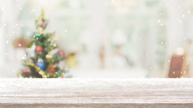 Leere holztischplatte auf unschärfe mit bokeh-weihnachtsbaum und neujahrsdekoration auf fensterbannerhintergrund mit schneefall - kann zur anzeige oder montage ihrer produkte verwendet werden.