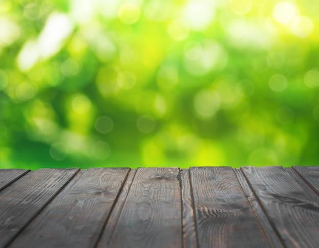 Leere holztischplatte auf unscharfem abstrakten grünen garten am morgen.